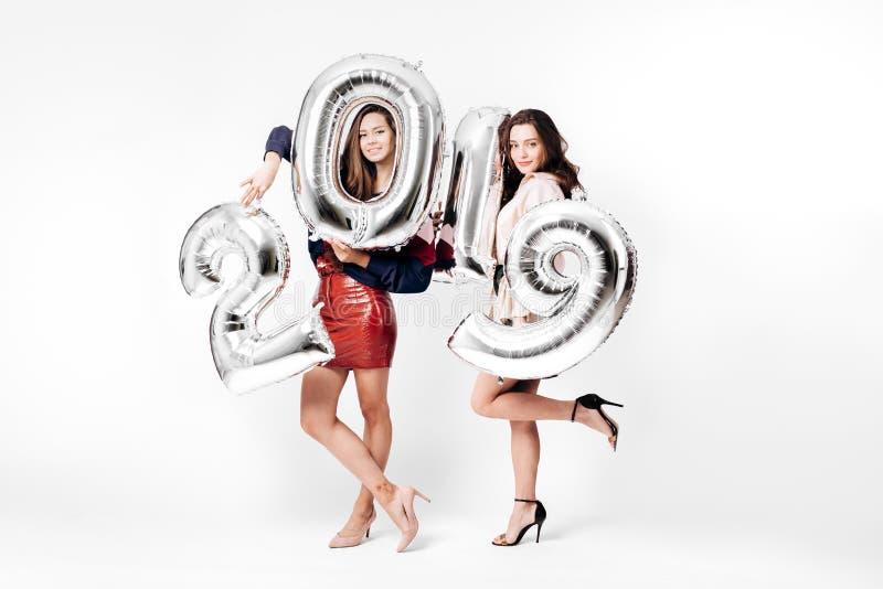 Deux belles filles habillées dans les vêtements intelligents élégants tiennent des ballons sous forme de numéros 2019 sur un blan images stock