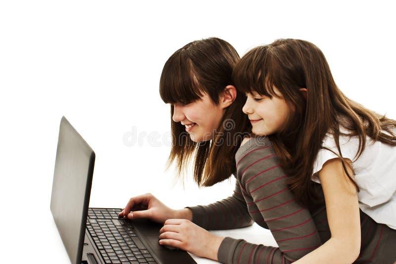 Deux belles filles heureuses à l'aide d'un ordinateur portatif photographie stock