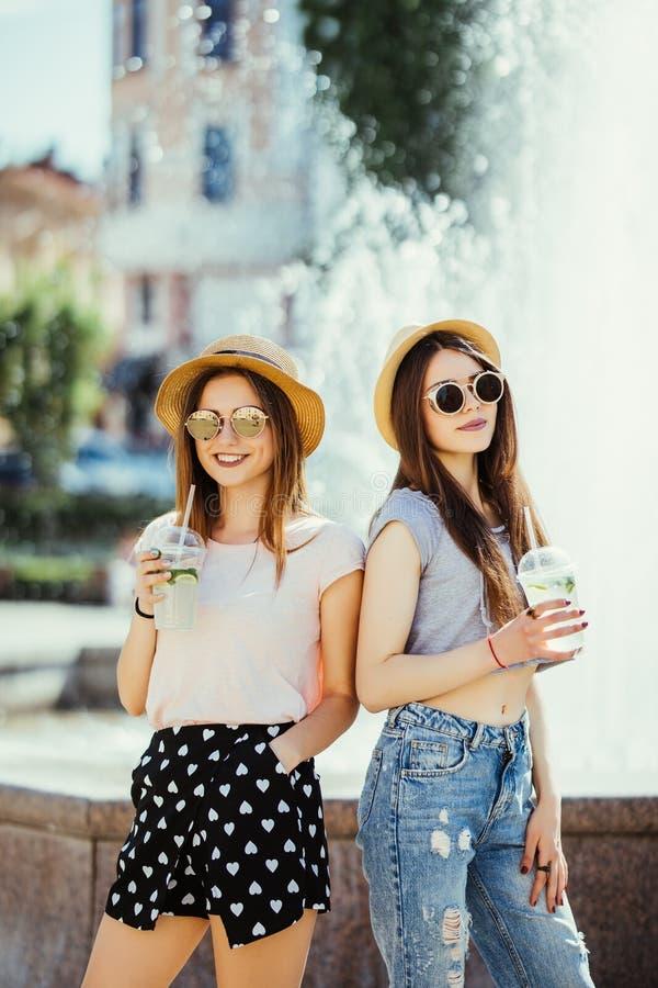 Deux belles filles heureuses avec des équipements d'été ayant l'amusement dans la rue avec des cocltails dans le jour d'été ensol images stock