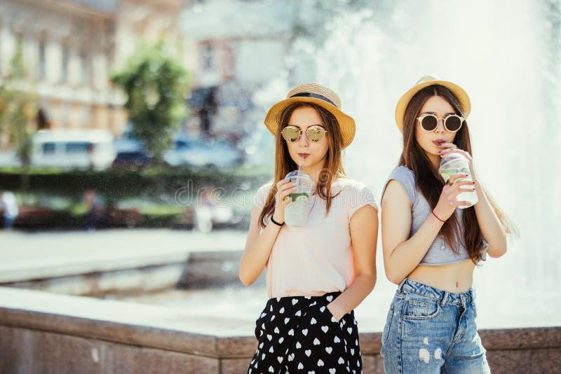 Deux belles filles heureuses avec des équipements d'été ayant l'amusement dans la rue avec des cocltails dans le jour d'été ensol photos libres de droits