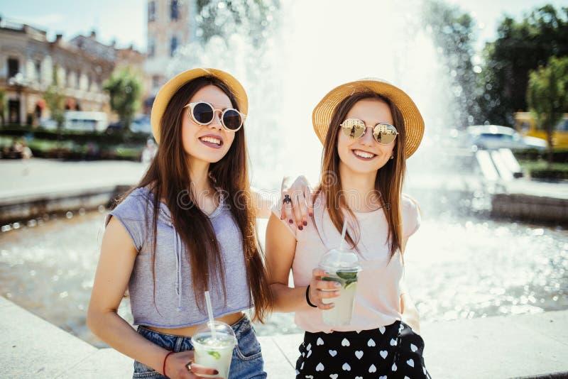 Deux belles filles heureuses ayant l'amusement boit le mojito dans le jour d'été ensoleillé marchant dans la rue près de la fonta photos libres de droits