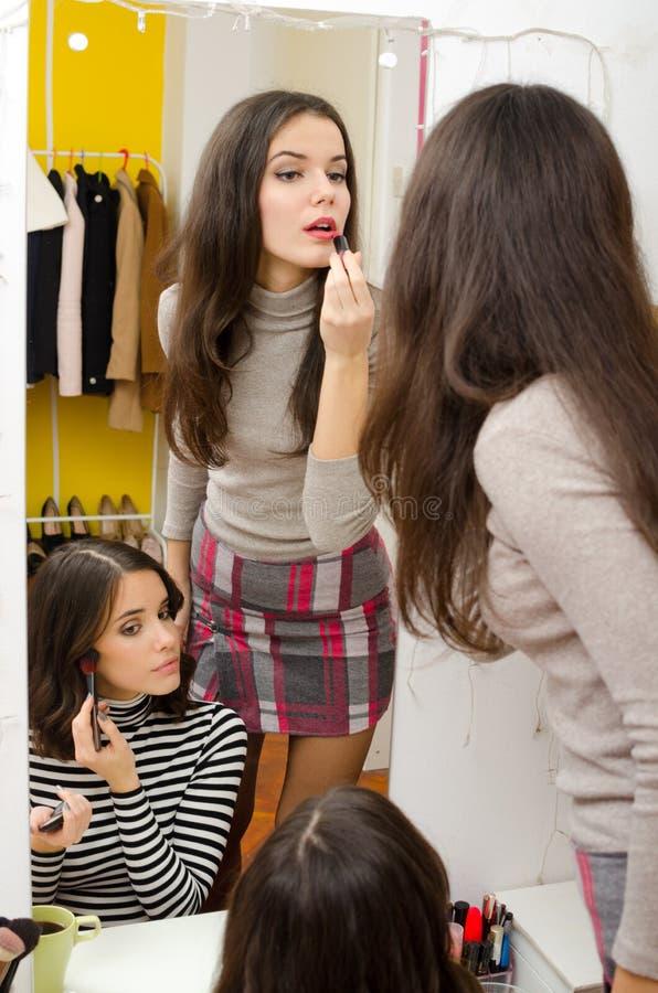 Deux belles filles mettant le maquillage devant le miroir à la maison images stock
