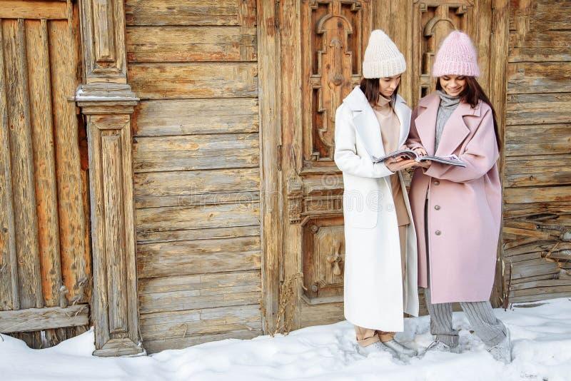 Deux belles filles portant l'hiver chaud vêtx la magazine de lecture dehors image stock