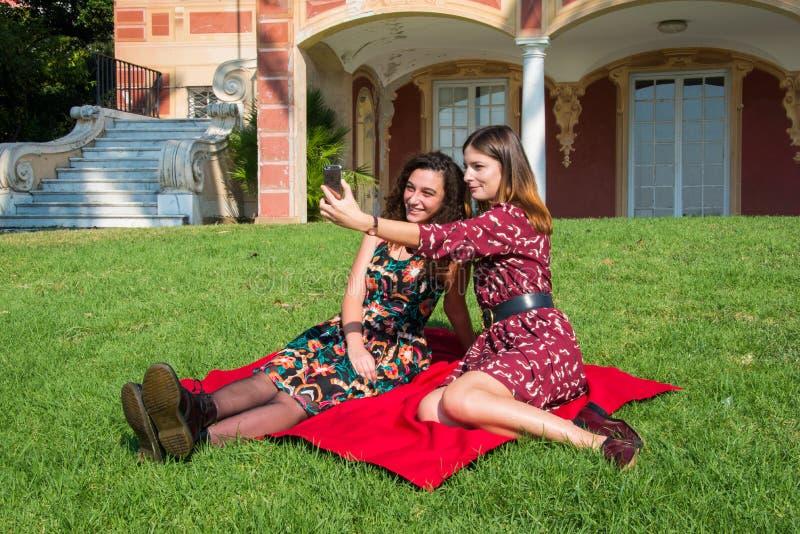 Deux belles filles prennent un selfie en parc avec un smartphone images libres de droits