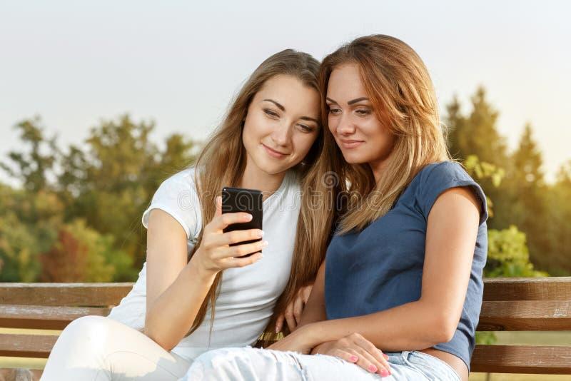 Deux belles filles se reposant sur le banc images stock