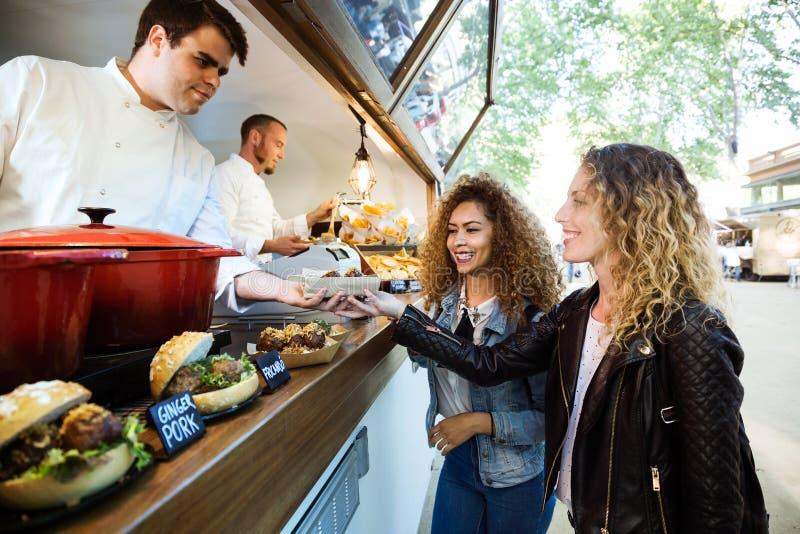 Deux belles jeunes femmes achetant des boulettes de viande sur un camion de nourriture photographie stock libre de droits