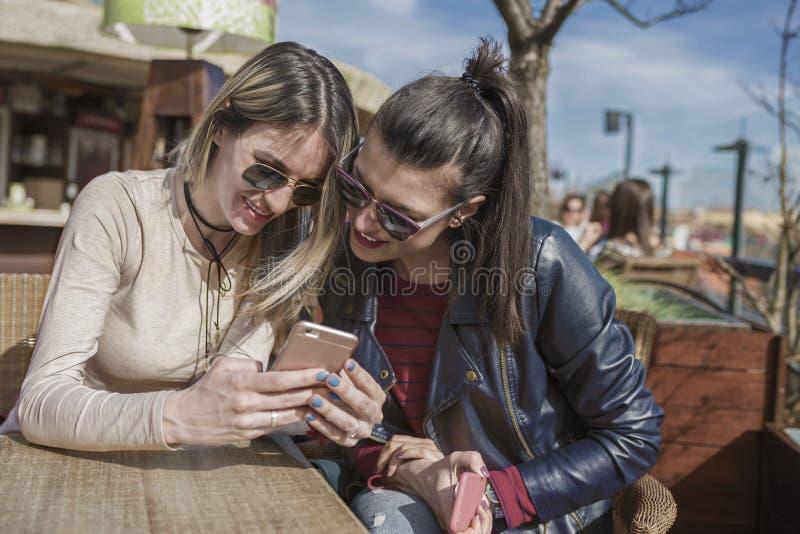 Deux belles jeunes femmes ayant l'amusement dehors tout en à l'aide de leurs smartphones image libre de droits