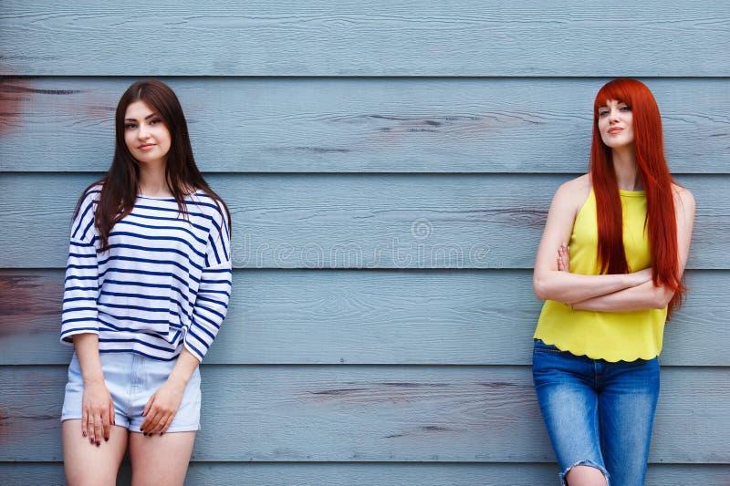 Deux belles jeunes femmes dans des vêtements sport lumineux posant l'outdoo image stock