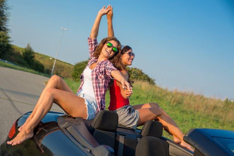 Deux belles jeunes femmes s'asseyant sur une voiture convertible appréciant le coucher du soleil photos stock