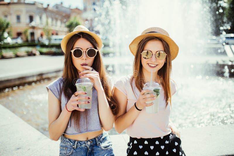 Deux belles jeunes filles dans la ville ensoleillée d'été buvant un cocktail se reposant près de la fontaine dans la rue d'été images libres de droits