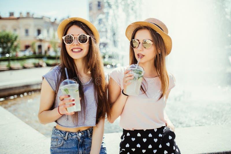 Deux belles jeunes filles dans la ville ensoleillée d'été buvant un cocktail se reposant près de la fontaine dans la rue d'été photographie stock libre de droits