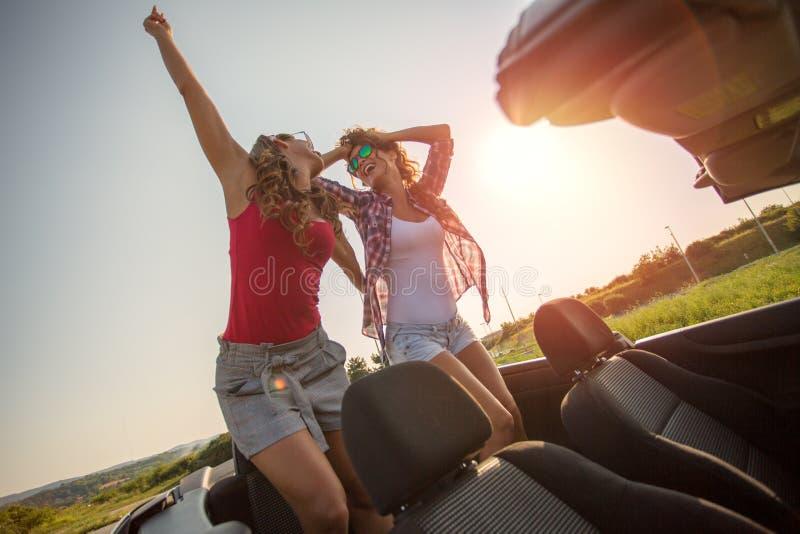 Deux belles jeunes filles dansant dans un convertible image libre de droits