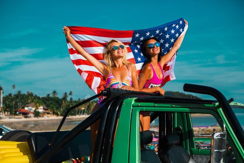 Deux belles jeunes filles incroyables dans des maillots de bain de bikini, voyageant autour d'une île tropicale dans un cabriolet images stock
