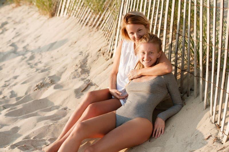 Deux belles jeunes filles s'asseyant sur la plage au coucher du soleil image libre de droits