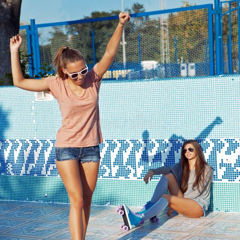 Deux belles jeunes filles utilisant des lunettes de soleil dans un regroupement vide image libre de droits