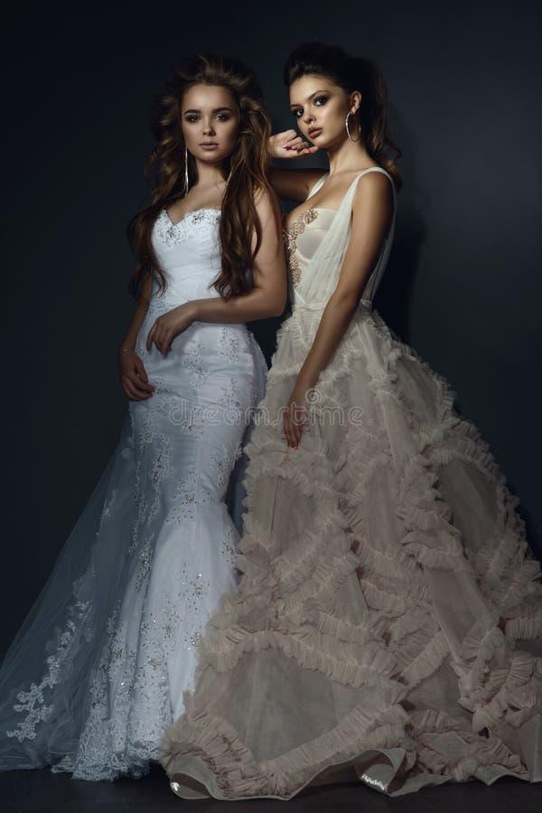 Deux belles jeunes mariées avec parfait composent et coiffure portant les robes les épousant luxueuses image stock