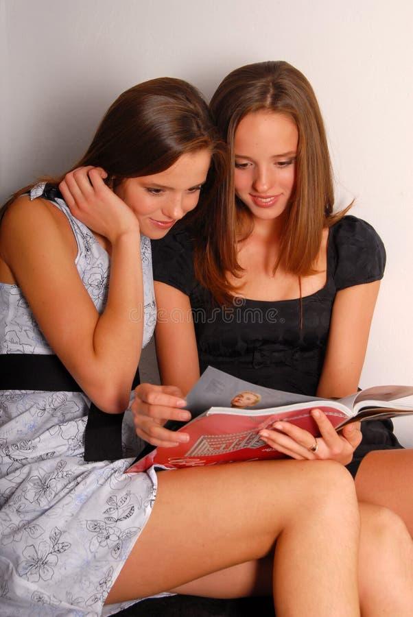 Deux belles jumeau-filles affichant un magazine photo libre de droits