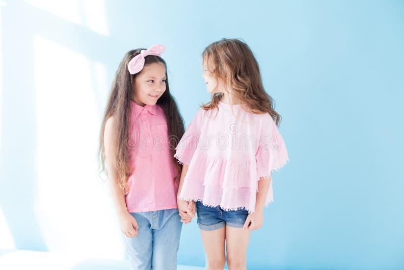 Deux belles petites filles dans l'amie rose de soeurs de vêtements photographie stock libre de droits