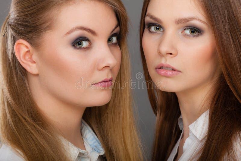 Deux belles poses de femmes, de blonde et de brune images stock