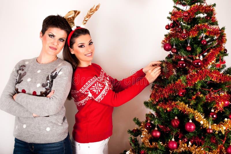 Deux belles poses de filles et décorent le grand arbre de Noël images stock