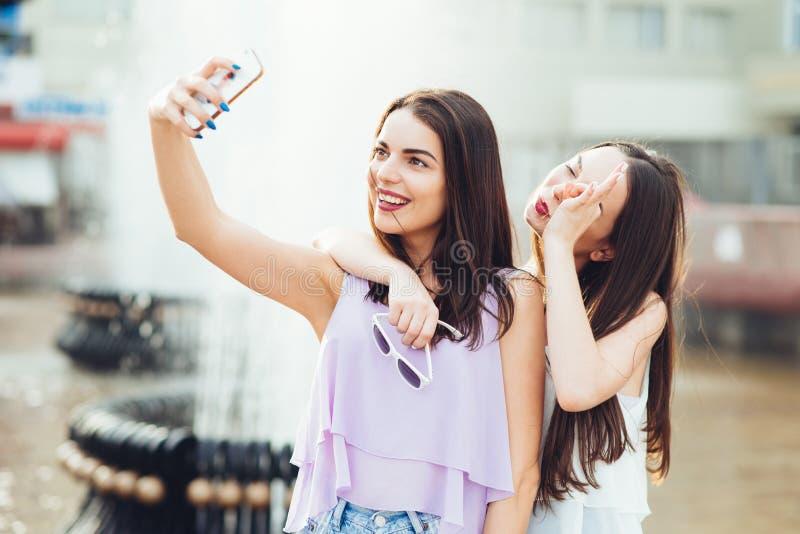 Deux belles soeurs font le selfie sur la rue images stock