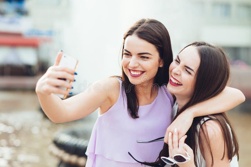 Deux belles soeurs font le selfie sur la rue photos stock