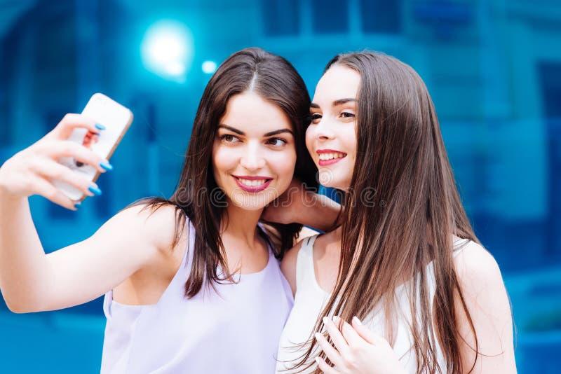 Deux belles soeurs font le selfie sur la rue image stock