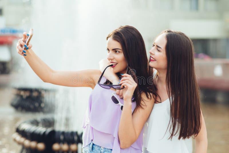 Deux belles soeurs font le selfie sur la rue photographie stock libre de droits