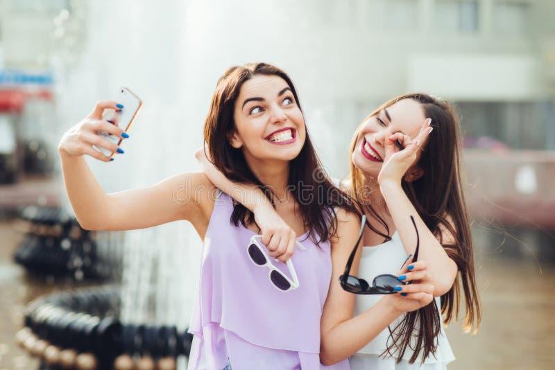 Deux belles soeurs font le selfie sur la rue photographie stock
