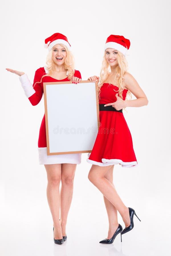 Deux belles soeurs heureuses jumelle le pointage sur le conseil vide images stock