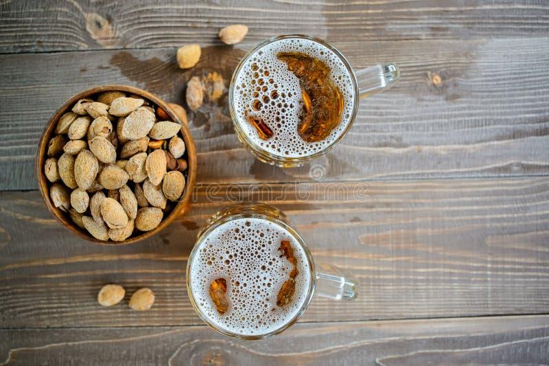 Deux bières d'Oktoberfest avec des pistaches sur une table en bois photo libre de droits