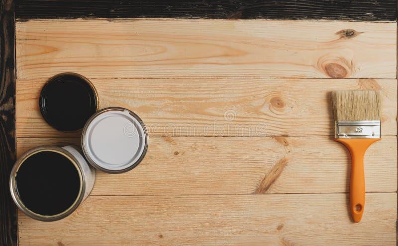 Deux bidons et brosses de peinture sur le fond en bois avec l'espace de copie au centre, vue supérieure images stock