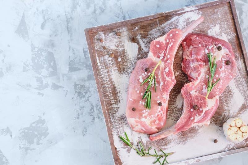 Deux biftecks de porc avec le poivre, l'ail et le romarin Morceaux de mensonge de viande crue sur un support en bois L'espace de  photos stock