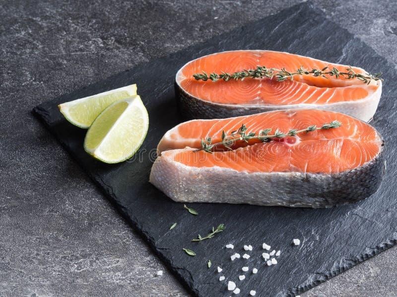 Deux biftecks saumonés crus sur le panneau d'ardoise images stock