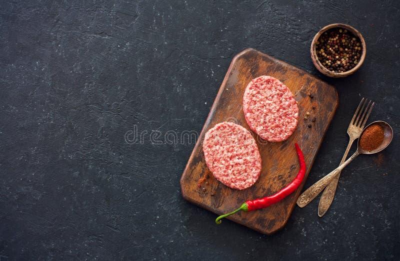 Deux bifteks, poivrons et vieilles cuillère, fourchette et planche à découper o image stock