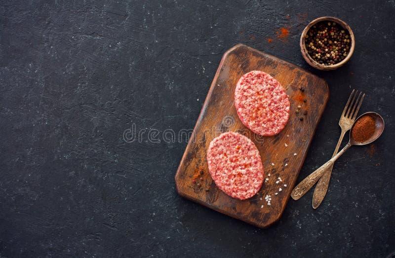 Deux bifteks, poivrons et vieilles cuillère, fourchette et planche à découper o photo libre de droits