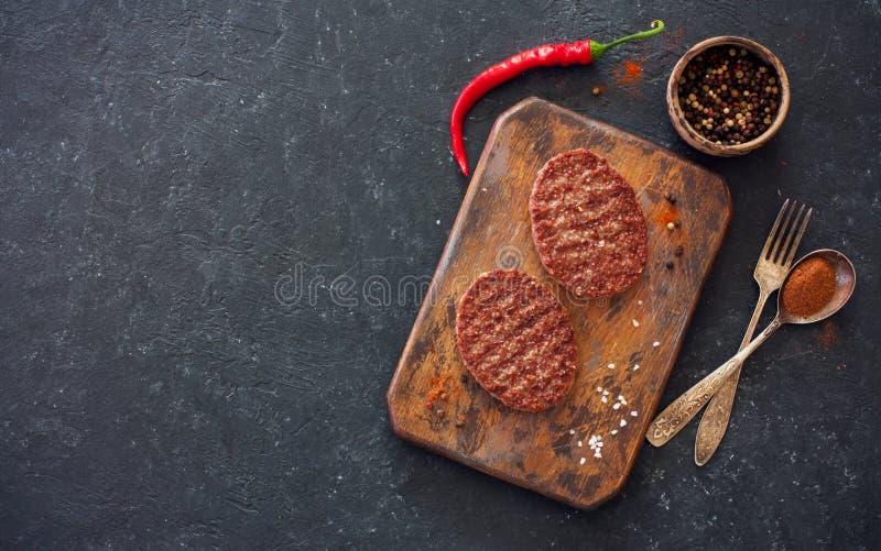 Deux bifteks, poivrons et vieilles cuillère, fourchette et planche à découper o photos stock