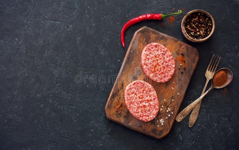 Deux bifteks, poivrons et vieilles cuillère, fourchette et planche à découper o images stock