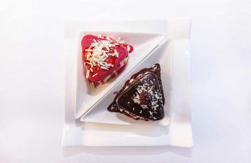 Deux biscuits avec un remplissage des baies et de la crème, d'un plat blanc et arrosé avec du chocolat blanc et foncé photographie stock