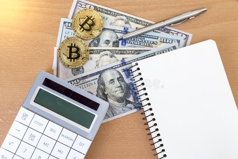 Deux bitcoins, journaux, stylos, et calculatrices d'or sur dollars US photo libre de droits