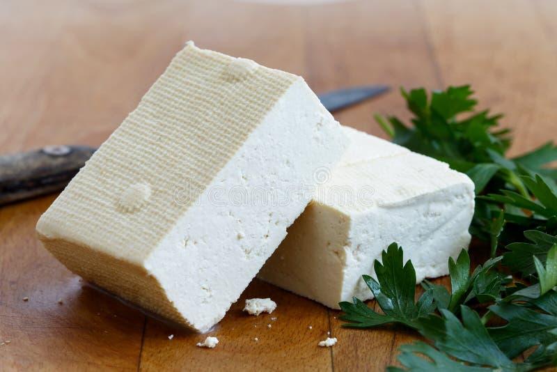 Deux blocs de tofu blanc avec le persil frais et le couteau rustique dessus photo stock