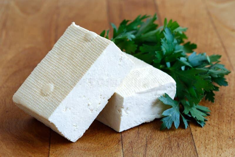 Deux blocs de tofu blanc avec le persil frais sur b de hachage en bois image libre de droits