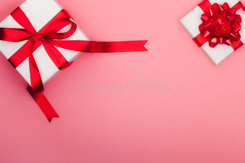 Deux boîte-cadeau blancs avec l'arc et le ruban rouges de satin sur la goupille en pastel photographie stock libre de droits