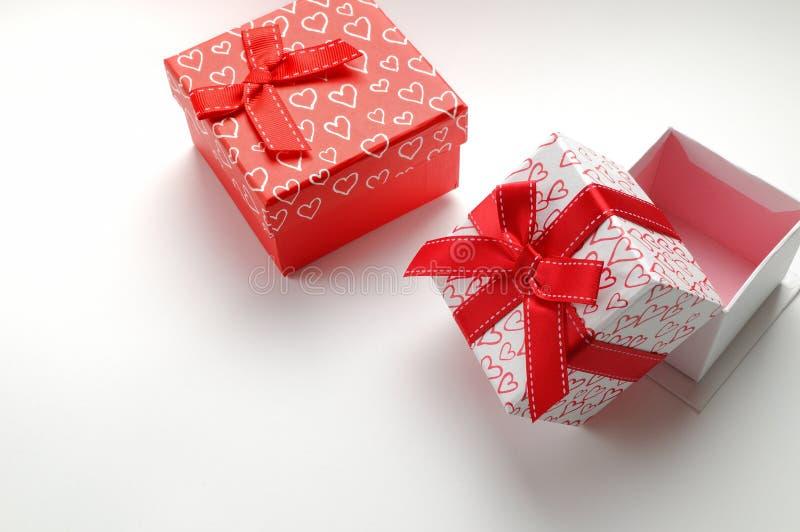 Deux boîte-cadeau décoratifs avec des coeurs imprimés ont isolé en haut à droite photographie stock