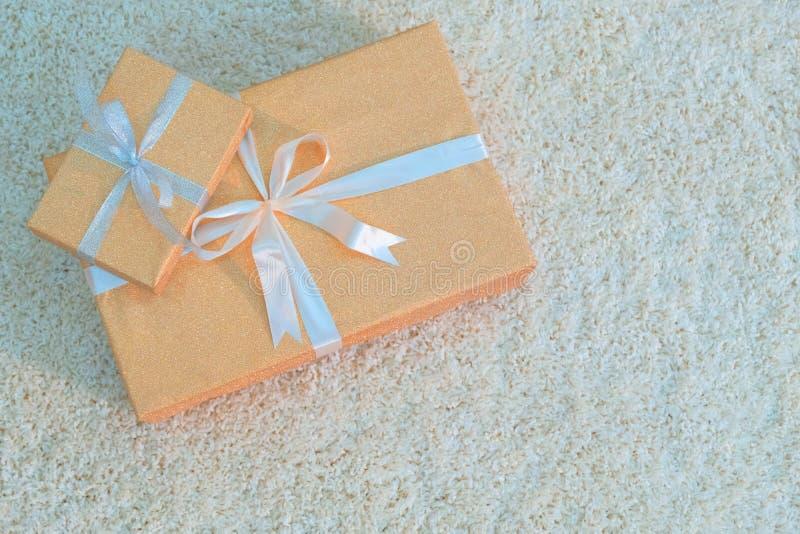 Deux boîte-cadeau de couleur d'or attachés avec des rubans se trouvent sur un tapis mou blanc Se préparant à la nouvelle année de photos stock