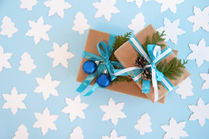 Deux boîte-cadeau enveloppés du papier de métier, le ruban bleu et blanc et les branches décorées de sapin, les boules bleues de  images stock
