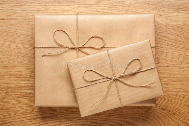 Deux boîte-cadeau enveloppés en papier d'emballage sur la table en bois photos stock