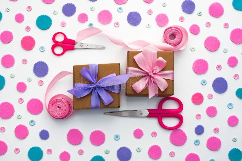 Deux boîtes de cadeau sont attachées avec le ruban de satin sur le fond avec les confettis colorés photo stock