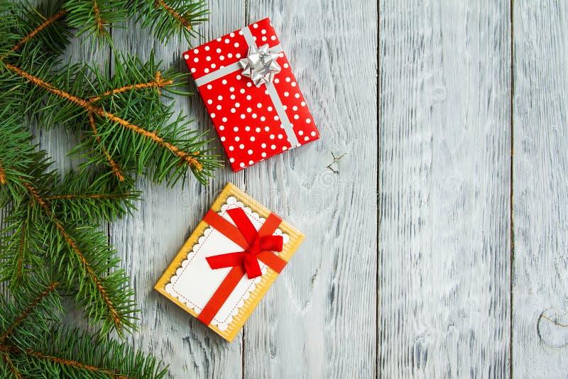 Deux boîtes de Noël de fête sur un fond en bois de vintage gris avec les branches d'arbre vertes image libre de droits