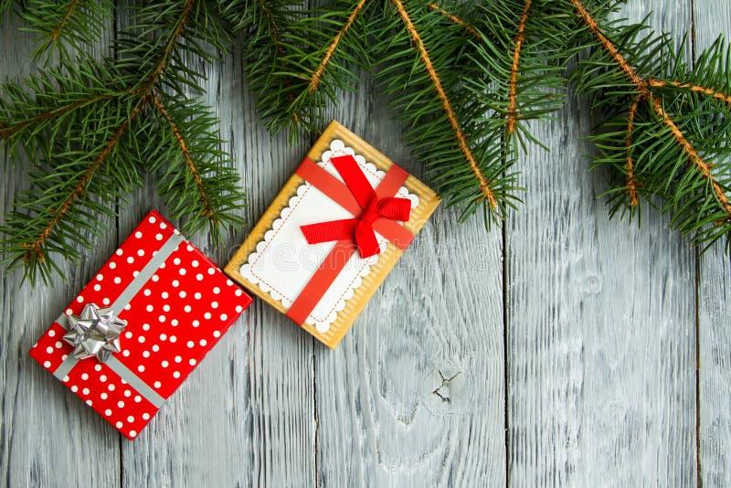 Deux boîtes de Noël de fête sur un fond en bois de vintage gris avec les branches d'arbre vertes image stock
